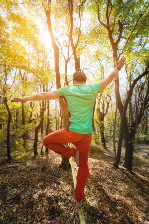 Wide angle male tightrope yogi balances on one leg in heron pose barefoot on slackline in autumn forest. The concept of outdoor sports and active life of people aged Zdjęcie Seryjne