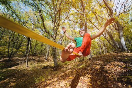 Wide angle male tightrope walker balancing while sitting barefoot on slackline in autumn forest. The concept of outdoor sports and active life of people aged Zdjęcie Seryjne