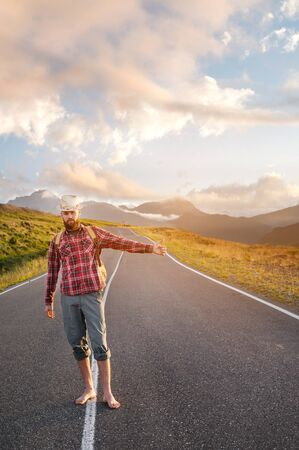 Stylish barefoot bearded male hitchhiker traveler in a hat and with a backpack walks along a suburban asphalt road in the mountains at sunset and stops the car with a hitch