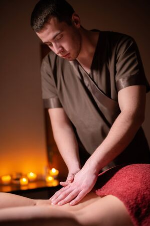 Mens premium luxury hip massage anti-cellulite wellness center. Male masseur doing leg massage to a female client in an office with dark light on a background of burning candles