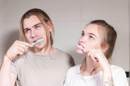 Young couple in bath brush teeth together, looking in mirror. Close-up 版權商用圖片