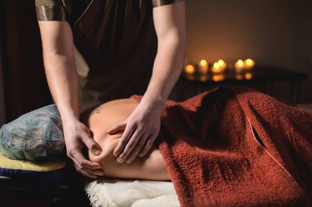Professional massage of the shoulder and trapezius muscle indoors with cozy dark lighting. Premium massage. Male physiotherapist massage therapist doing upper back massage to a female client