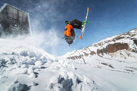 Low angle view athlete skier in an orange jacket does a back flip with flying powder of snow against a clear blue sky and snow-capped mountains of the Caucasus. Winter Extreme Sports Concept Stockfoto