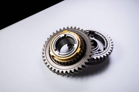 New parts on a gray background. Gears of gear shifting torque transmission. Conceptually mechanical background. Shiny gear box gear teeth Imagens