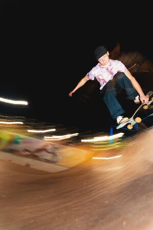 A young skater at night in a skatepark does the trick on the railing. X-ray culture nightlife concept Foto de archivo
