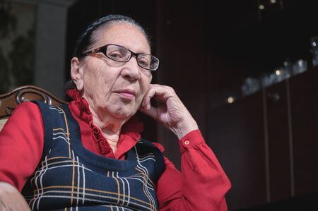 A sad old woman with glasses sits in an armchair in a dark room and looks sadly at the camera. The concept of isolating the protection and rescue of older people from the virus during a pandemic