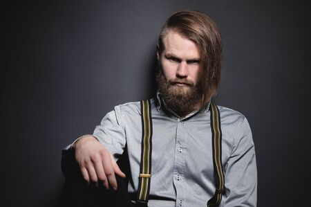 Contrasting low key portrait of a bearded long-haired stylish brutal man in a gray shirt with suspenders sternly looks at the camera. The concept of style and brutal beauty in the studio