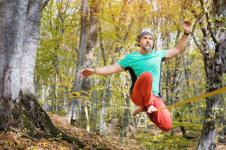 A bearded man aged walks along a slackline in the autumn forest on a sunny afternoon. The concept of Leisure and Recreation of active middle-aged people Stock Photo