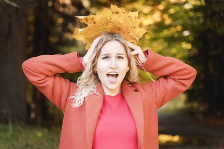 Portrait of an attractive young blonde in a red coat with a bouquet of yellow leaves in her hand screaming holding on to her head.