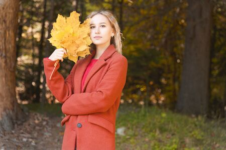 Portrait of an attractive young blonde in a red coat with a bouquet of yellow leaves in her hand. The concept of dreaming about forest walks during a virus pandemic. Autumn fashion in the forest Imagens
