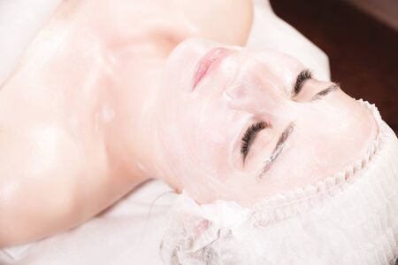 A young attractive girl in a cosmetologist s office with her face covered in a cosmetic rejuvenating white mask with a brush applied lies and relaxes. Facial skin care concept