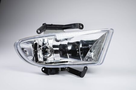 A one of new embedded in the front bumper fog lights on a gray background. New modules of additional lighting spare parts for the car