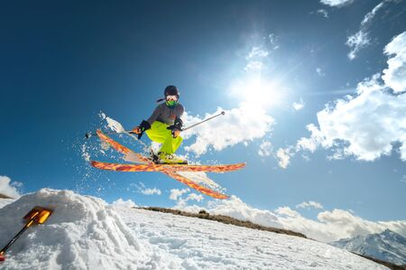 Girl skier in flight after jumping from a kicker in the spring against sun and blue sky. Close-up wide angle. Reklamní fotografie