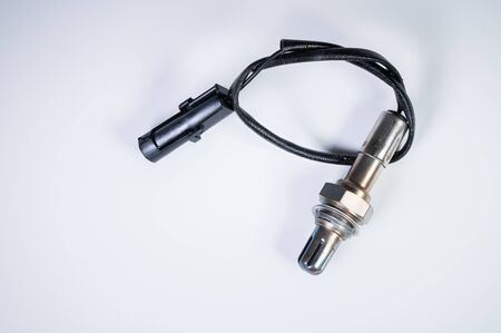 The oxygen sensor is a new lambda sensor. Spare parts on the car on a gray gradient background