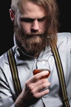 An attractive man with a long bang beard and a mustache sitting against the wall sniffs the scent of an alcoholic beverage in a glass that holds his hand.
