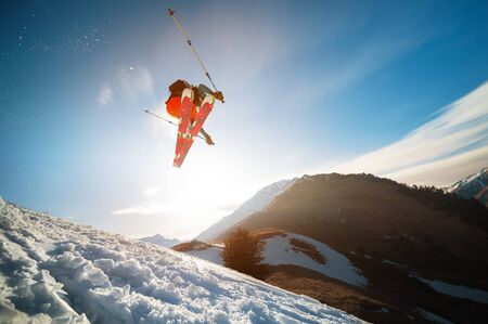 man skier in flight after jumping from a kicker in the spring against the backdrop of mountains and blue sky. Close-up wide angle. The concept of closing the ski season and skiing in spring