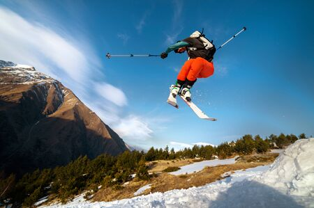 man skier in flight after jumping from a kicker in the spring against the backdrop of mountains and blue sky. Close-up wide angle. The concept of closing the ski season and skiing in spring Imagens