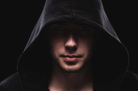 Close-up portrait of a courageous man in a deep dark hood on a black background. The concept of secrecy of secrets and people hiding from the government. Hackers and thieves. Low key Stockfoto