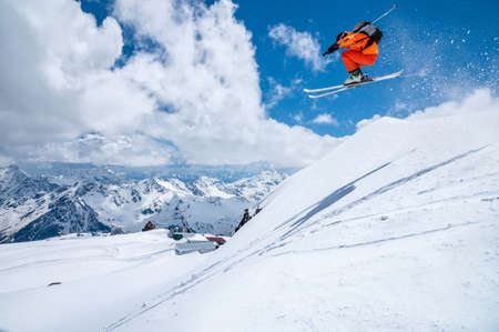 A male skier in an orange suit flies in the air after jumping from a snow sweep high in the Caucasian mountains on a sunny day amid snow-capped mountains of blue sky and white clouds