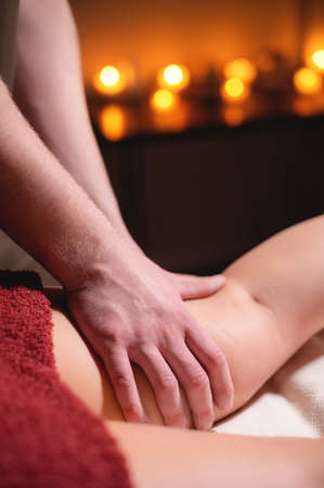 Close-up professional massage of the female hip in the dark room of the spa salon against the background of burning candles. The concept of hip muscle health Banque d'images