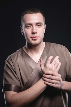 Portrait of a strong and large male masseur in special clothes with a finger at the temple reads your chin and knows all your diseases on a black background in the studio. Stock Photo