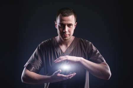 A courageous male masseur makes a passage with his hands, lighting spheres of blue fire between the palms, as the energy of healing and the power of energy practices.