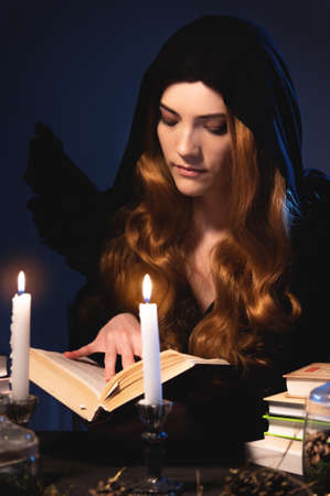 Medium closeup attractive Caucasian girl with golden long hair in a black hood sits at a table and leafs through a book. Costume with wings. Candles are burning. Halloween celebration concept