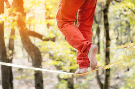 A man in orange sports trousers walks balancing on a taut slackline close-up