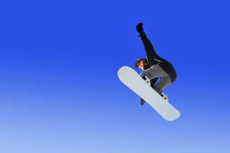 Snowboarder girl does a trick in jumping with a grab against the blue sky. Blue gradient background isolated athlete in flight