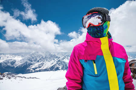 Portrait of a girl skier in a multi-colored bright jacket in a ski mask with her face closed on a sunny day against the backdrop of snow-capped Caucasian mountains and clouds Banco de Imagens