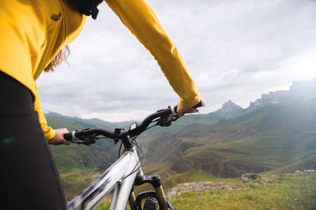 A close-up of the girls hand cyclist on the handlebars of a mountain bike against the backdrop of epic rocks and mountains. Mountain bike. Girls cyclist