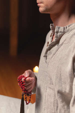 A close-up of the monks hands hold red rosaries against the background of the wooden floor of the practice room and lit candles Stok Fotoğraf
