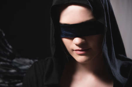 Portrait of an attractive young woman in a hood and black cape with a blindfold. Low key sexy caucasian girl justice and role playing on black and gray background