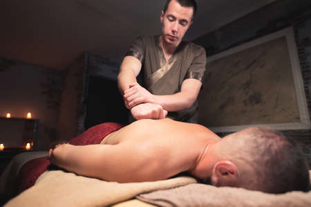 Young man masseur doing sports massage to a muscular athlete. Professional back massage in a dark room with candles. Relaxation and spa recovery of the muscular apparatus