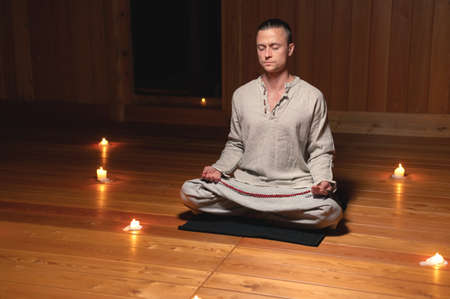 A man in clothes for practice and meditation sits in a lotus pose and holds red rosary to concentrate attention in a wooden room with dim light