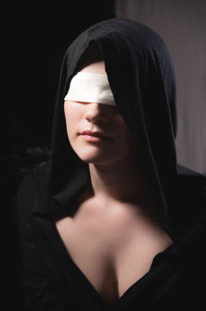 Portrait of an attractive young woman in a hood and black cape with a blindfold. Low key sexy caucasian girl justice and role play on black and gray background Stok Fotoğraf