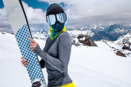 Portrait of a slender girl in a buff and balaclava in a ski mask and hat with a closed face next to skis on the background of snow-capped epic mountains.