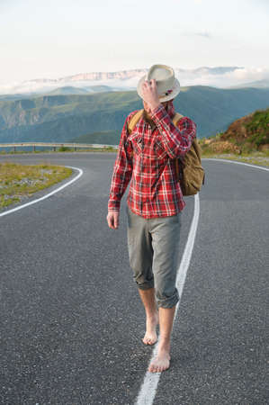 A young bearded hipster in a shirt hat and barefoot walks along a country road in the mountains. Hitchhiking and free travel