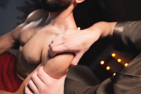 A male masseur does a sports shoulder massage to a muscular male athlete in a room with a contrasting dark light. Professional sports massage