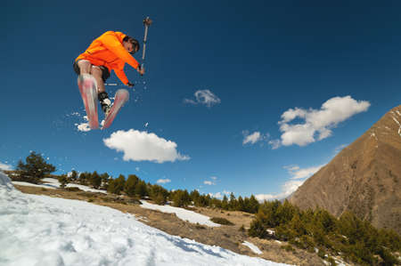 A young stylish man in sunglasses and a cap performs a trick in jumping with a kicker of snow against the blue sky and the sun on a sunny day.