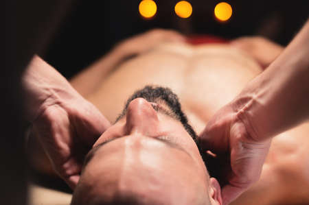 A male massage therapist makes a client athlete a man a neck massage in a dark cozy spa massage salon. Professional sports massage