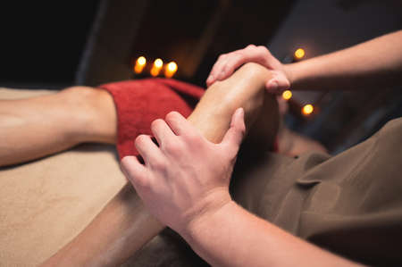 Male masseur doing sports massage of the lower leg to the athlete in the massage spa salon