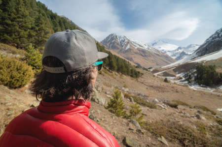 A long-haired young man in a red down jacket and grey cap in sunglasses stands with his back to the camera and looks at a mountain gorge with snow-capped peaks in the distance
