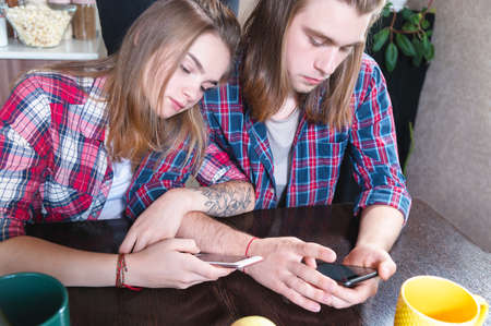 Young couple man and woman with long hair are sitting at the kitchen table in the kitchen and using their smartphones while buying food on the internet Stok Fotoğraf