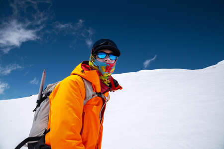 Portrait of a stern climber skier in sunglasses and a cap with a ski mask on his face. against the backdrop of Mount Elbrus