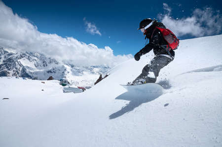 Girl snowboarder with a backpack on a snowy fresh slope against the backdrop of high mountains and blue sky. Winter kinds of extreme sports. Snowboard