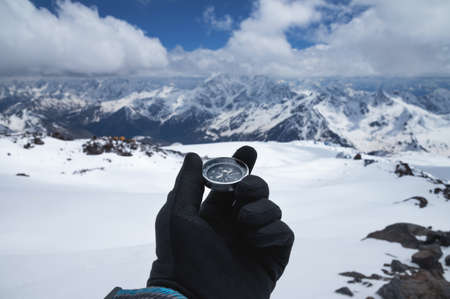 A metal magnetic compass in the hand of a traveler in a black glove against the backdrop of snow-capped mountains