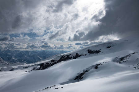 Evening high mountain scenery snow-covered rocky steep mountains of the main mountain range of the northern Caucasus