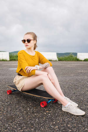 A young attractive girl in a yellow sweater shorts and sunglasses with a tattoo on her arm sits on a longboard behind a suburban asphalt pad Stok Fotoğraf