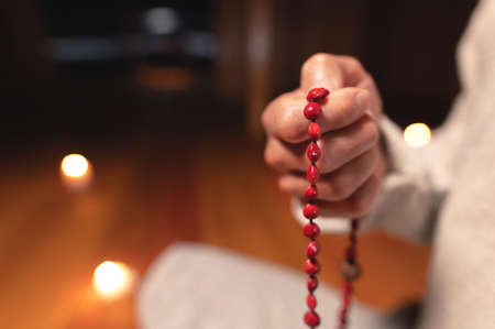 close-up man in clothes for practice and meditation sits in a lotus pose and holds red rosary to concentrate attention in a wooden room with dim light Stok Fotoğraf